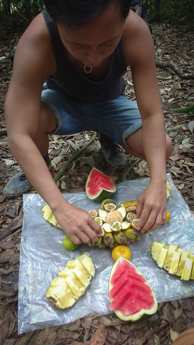 Trekking guide jungle bukit lawang preparing the dessert consisting of fruit