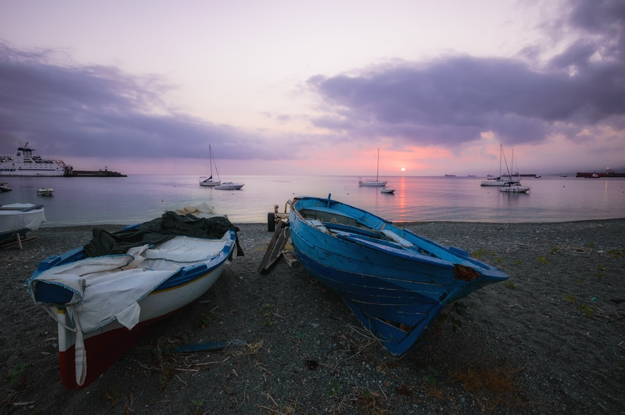 Boats on the sand of Milazzo at sunrise Sicily Italy