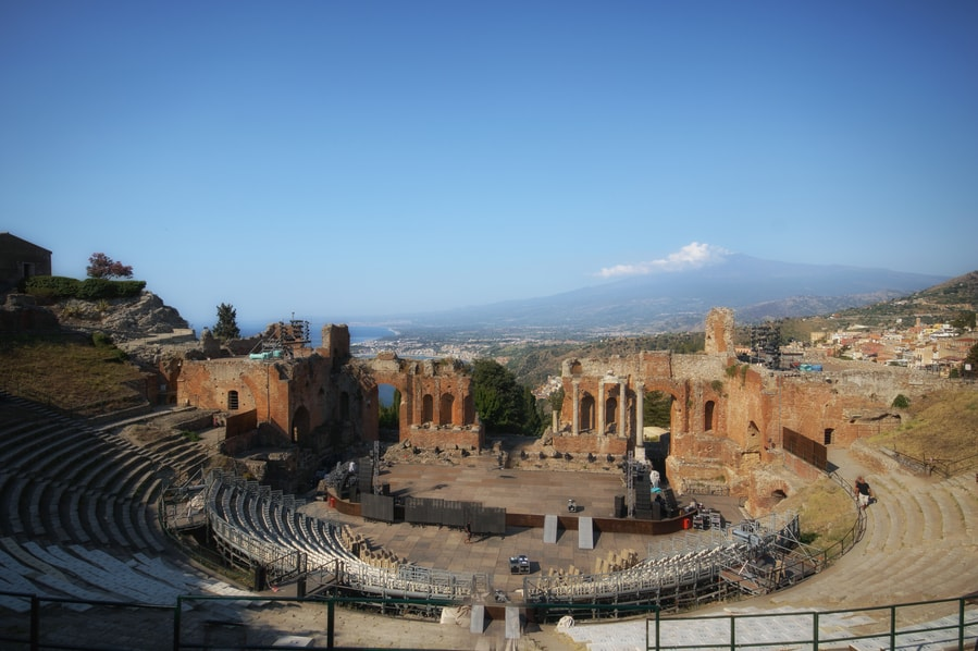 The Etna volcano in the background at the Teatro Antico in Taormina in one day Sicily Italy