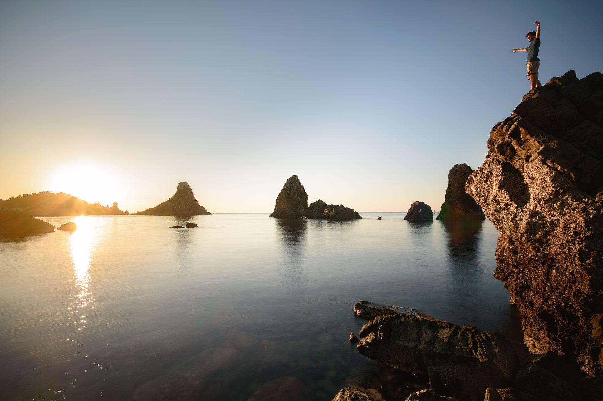 Amanecer desde una roca de los Faraglioni Sicilia Aci Trezza Italia
