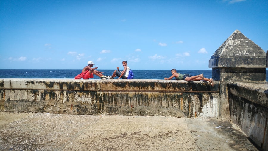 Children enjoying the waves on the Malecon of Havana Cuba