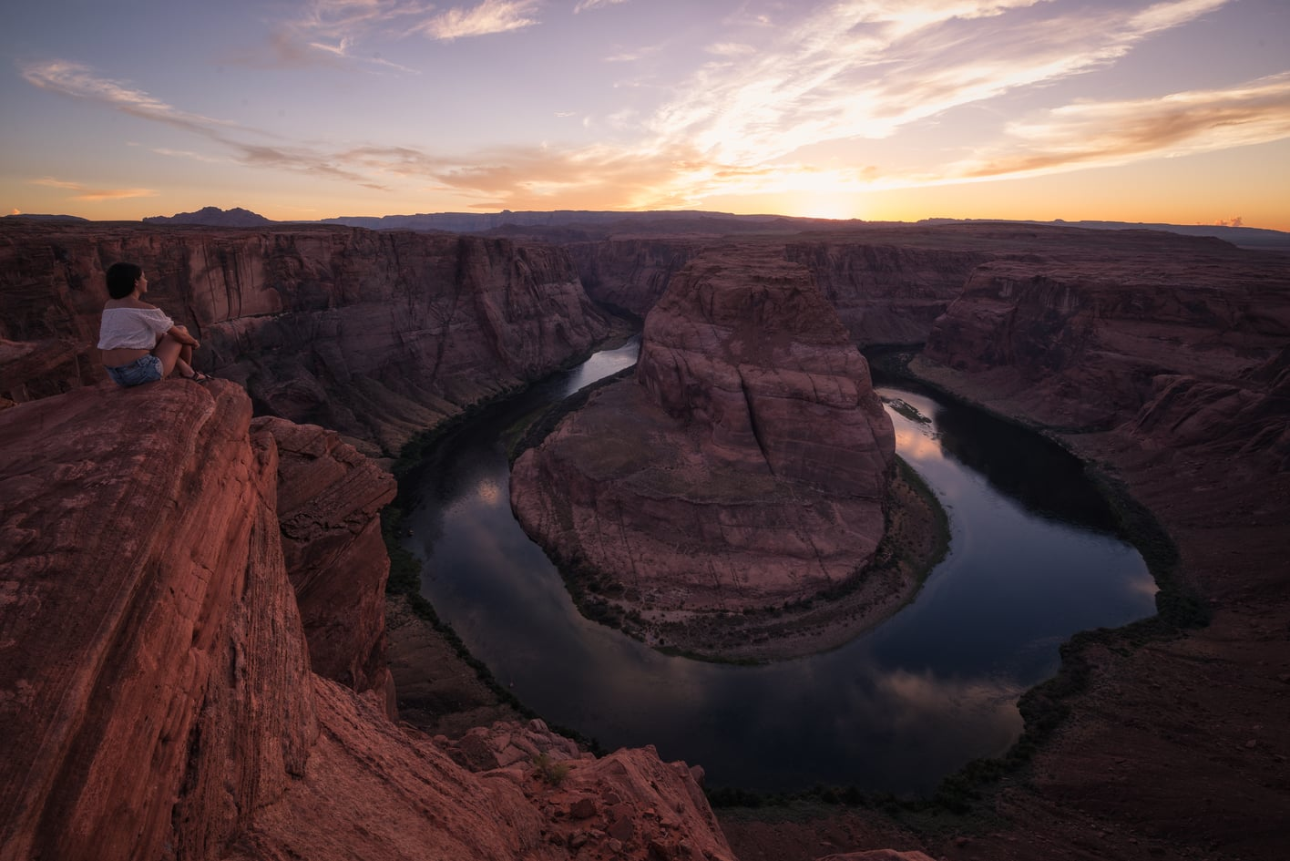 horseshoe bend at sunset, girl sit on the cliff