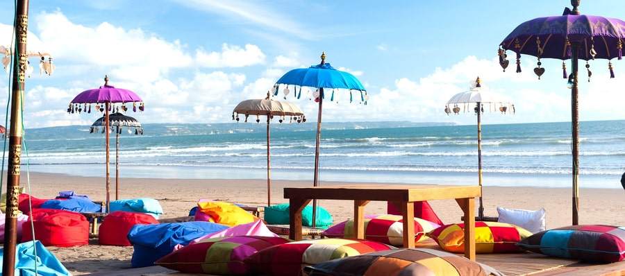 beach colored umbrellas in kuta, one of the best areas to stay in Bali