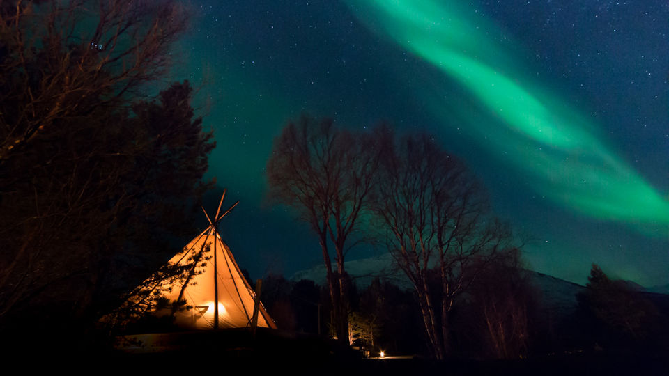 aurora boreal display under a tipi in norway